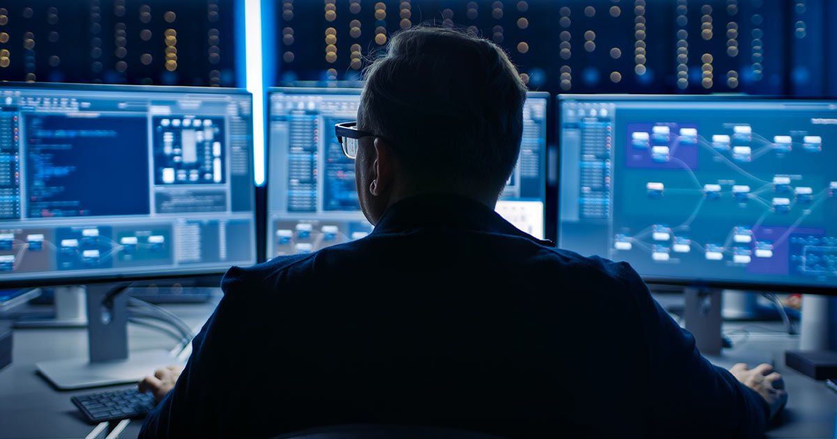 Cybersecurity expert working with three computer monitors