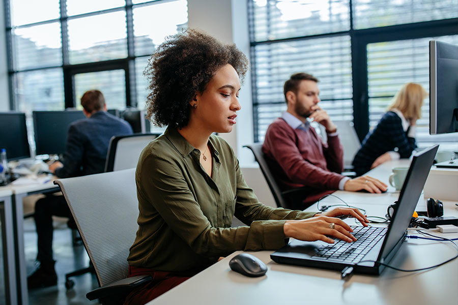 Woman in office focused on laptop