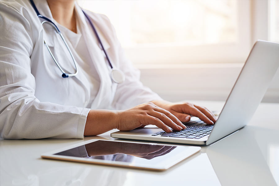 Doctor using a laptop with tablet on table