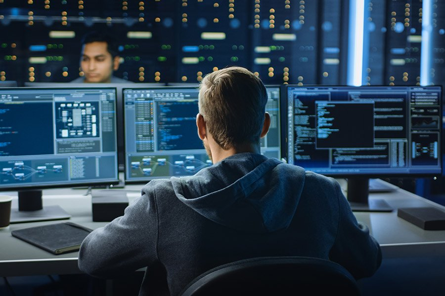 Cybersecurity technician facing three computer monitors