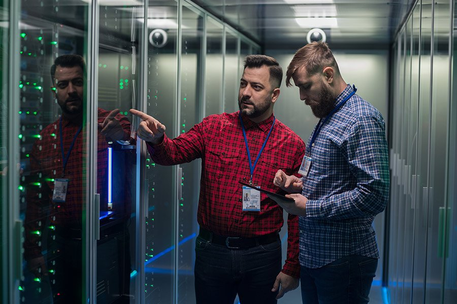 Two men inspecting server room