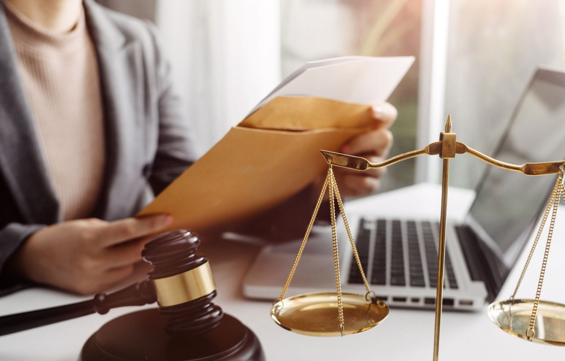 lawyer looking at documents with gavel and laptop on desk