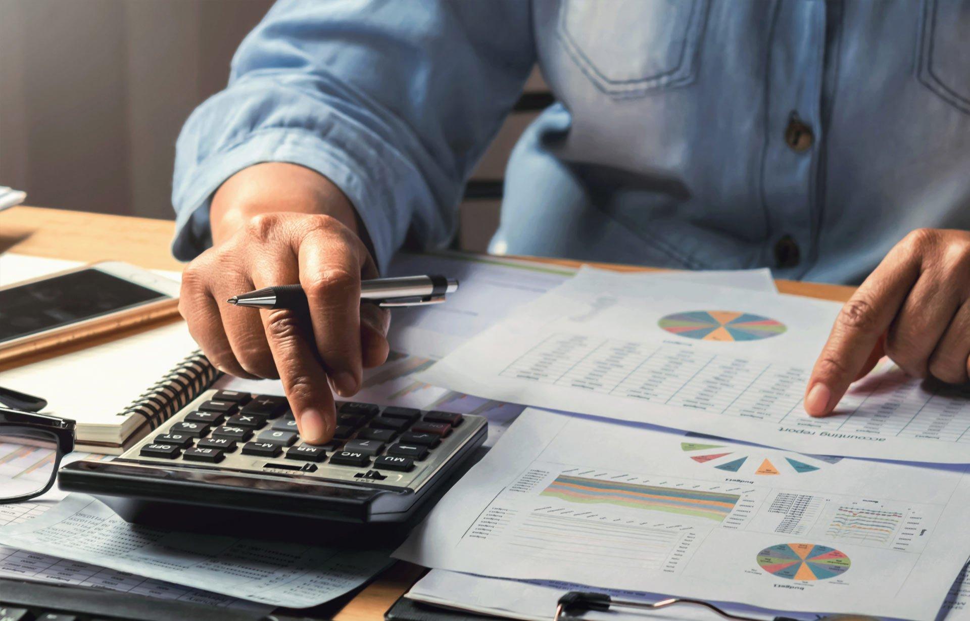 man doing accounting work using calculator